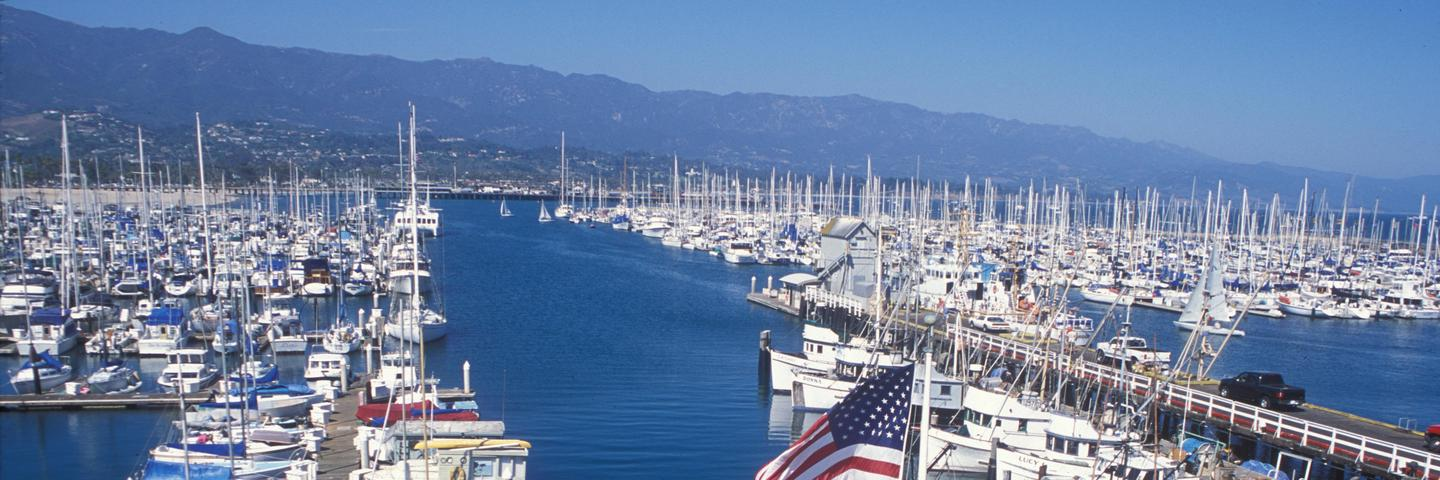 View of harbor with boats and tall mountains.View from the deck of the Outdoors Santa Barbara Visitor Center.
