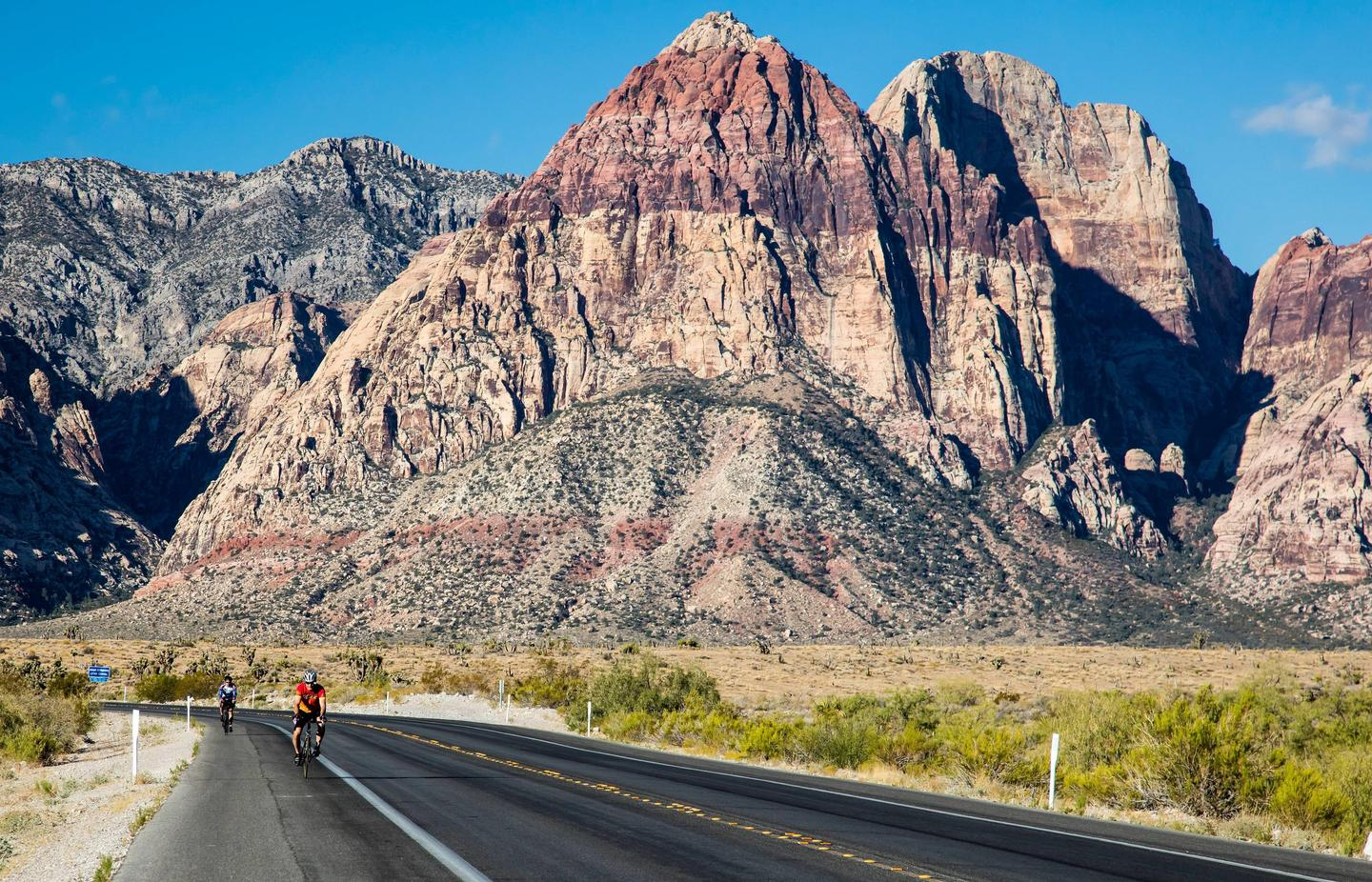 Cyclists ride along the road near Red Rock Canyon. Cyclists enjoy the views of Red Rock Canyon.
