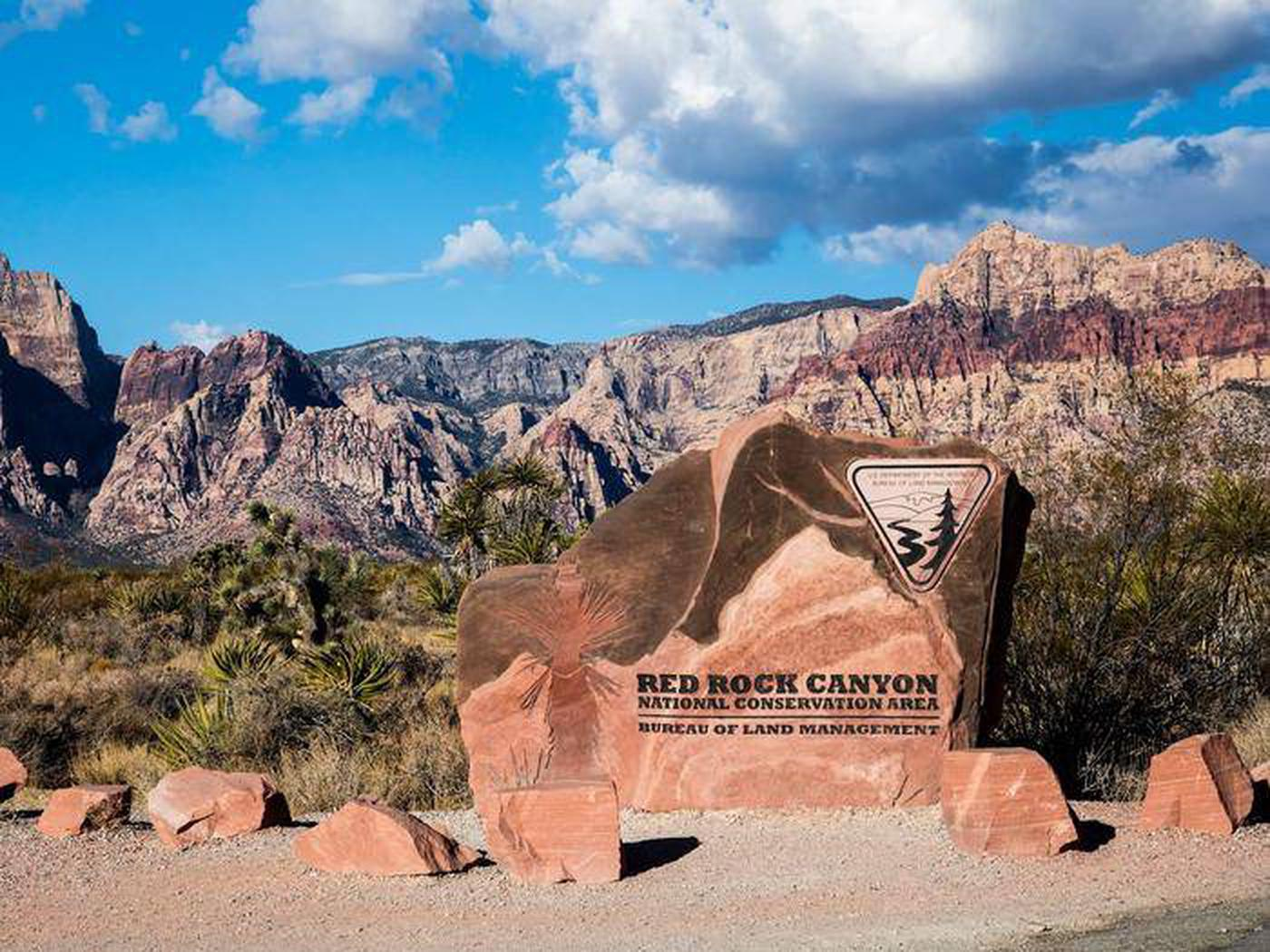 Red Rock Canyon entrance sign with mountains in the background. Red Rock Canyon welcomes visitors.