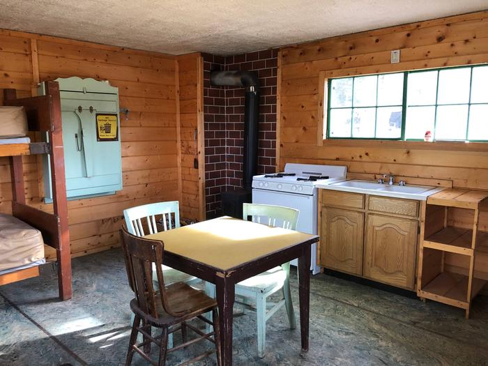 Cabin interior showing gas range, wood stove, table and dry sink.Cabin Interior