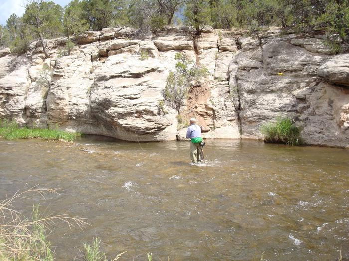 A fisherman works under cliffs on Beat 3 of the Pecos River.Pecos National Historical Park - Beat 3 of the Pecos River.