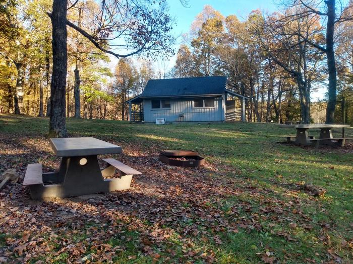 View of a campsite and a comfort station.Comfort stations with cold running water and flush toilets are available in each loop.