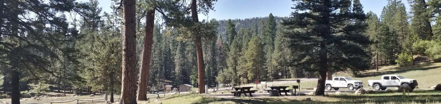 A view of the mountains with picnic tables and vehicles in the background.Clear Creek Campground View