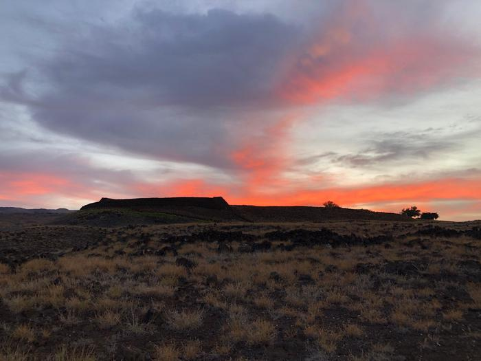 SunriseSunrise with a bright orange red glow rising above Pu'ukoholā Heiau.