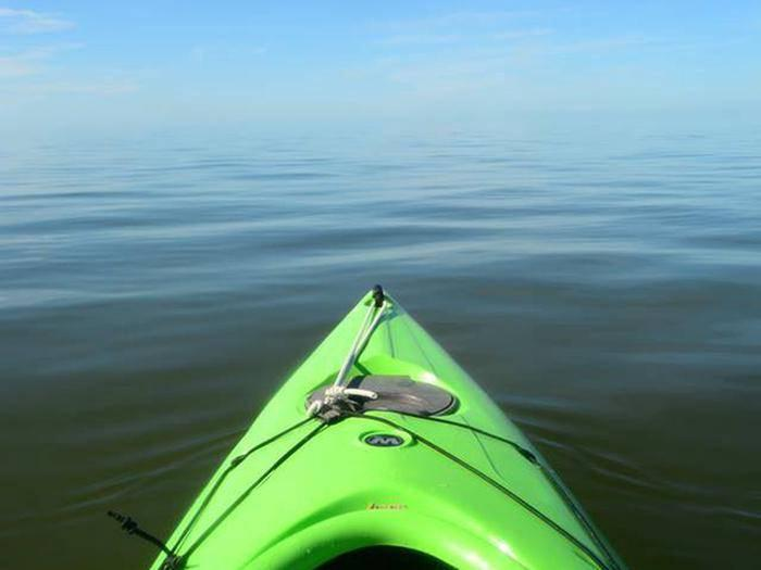 The sky and Gulf of Mexico blend without a horizon with a green kayak in foregroundA green kayak paddles towards the Gulf of Mexico