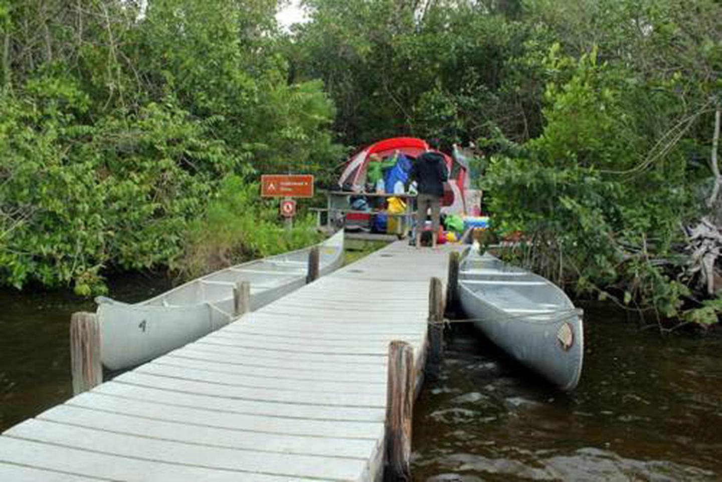 A dock leads to a ground campsite with people setting up a tentLostman's Five Ground Campsite