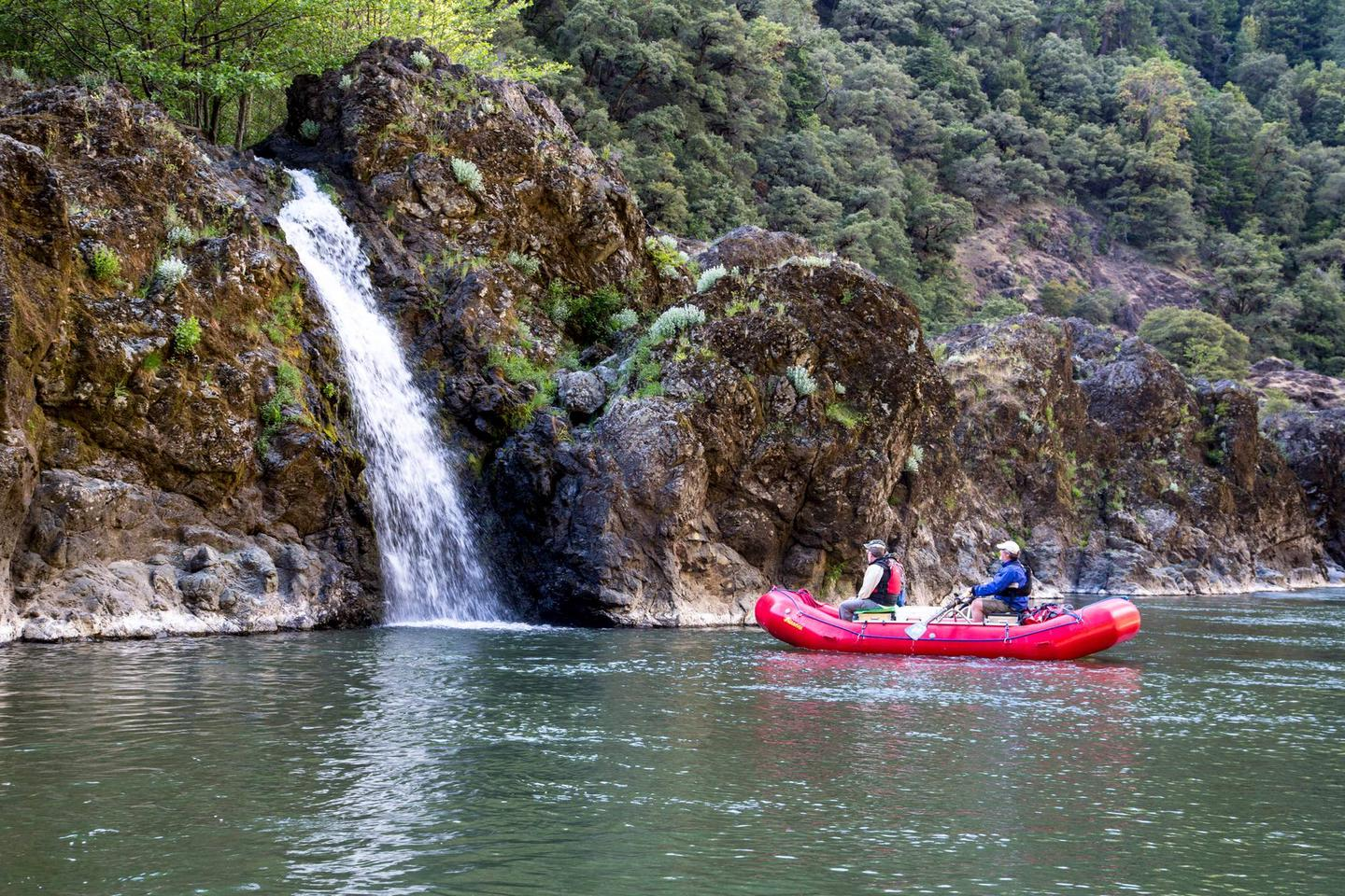 Two boaters in a red raft observe a small waterfall tumbling over mossy rocks into the Rogue River.Small waterfall on the Rogue Wild & Scenic River.