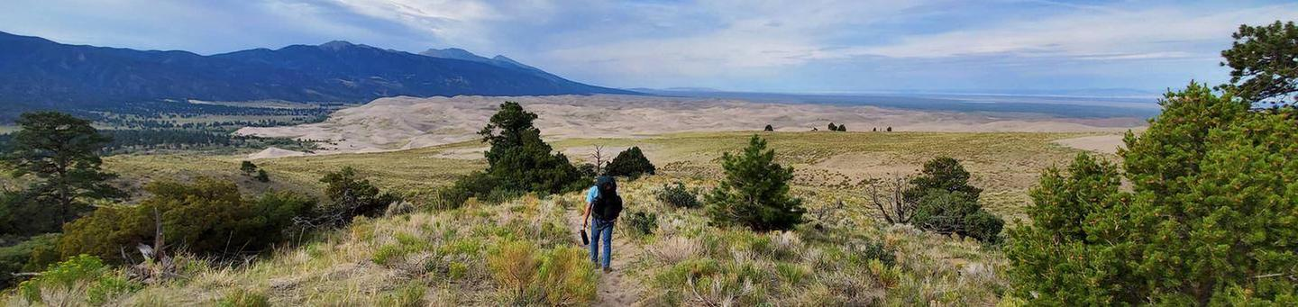A backpacker walking along a sandy trail overlooking the dune field .The sandramp trail can offer spectacular views of the Sangre de Cristo Mountains and the dunefield, such as this view from near the Aspen backcountry site.