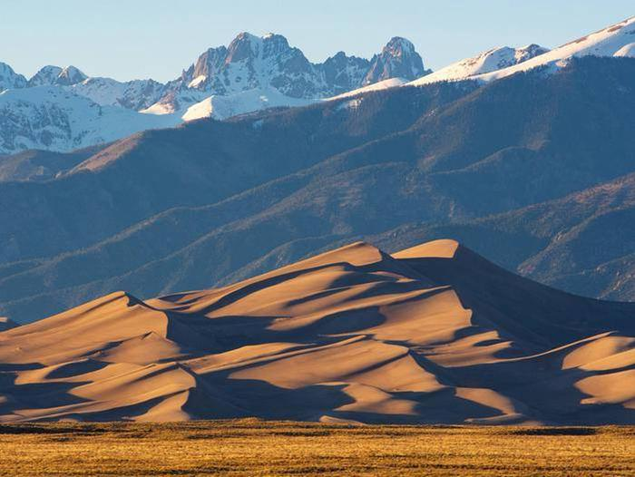 A sand dune rises above the grasslands with the Sangre de Cristo Mountains behind them.The dune field offers a unique camping experience to those looking for solitude.