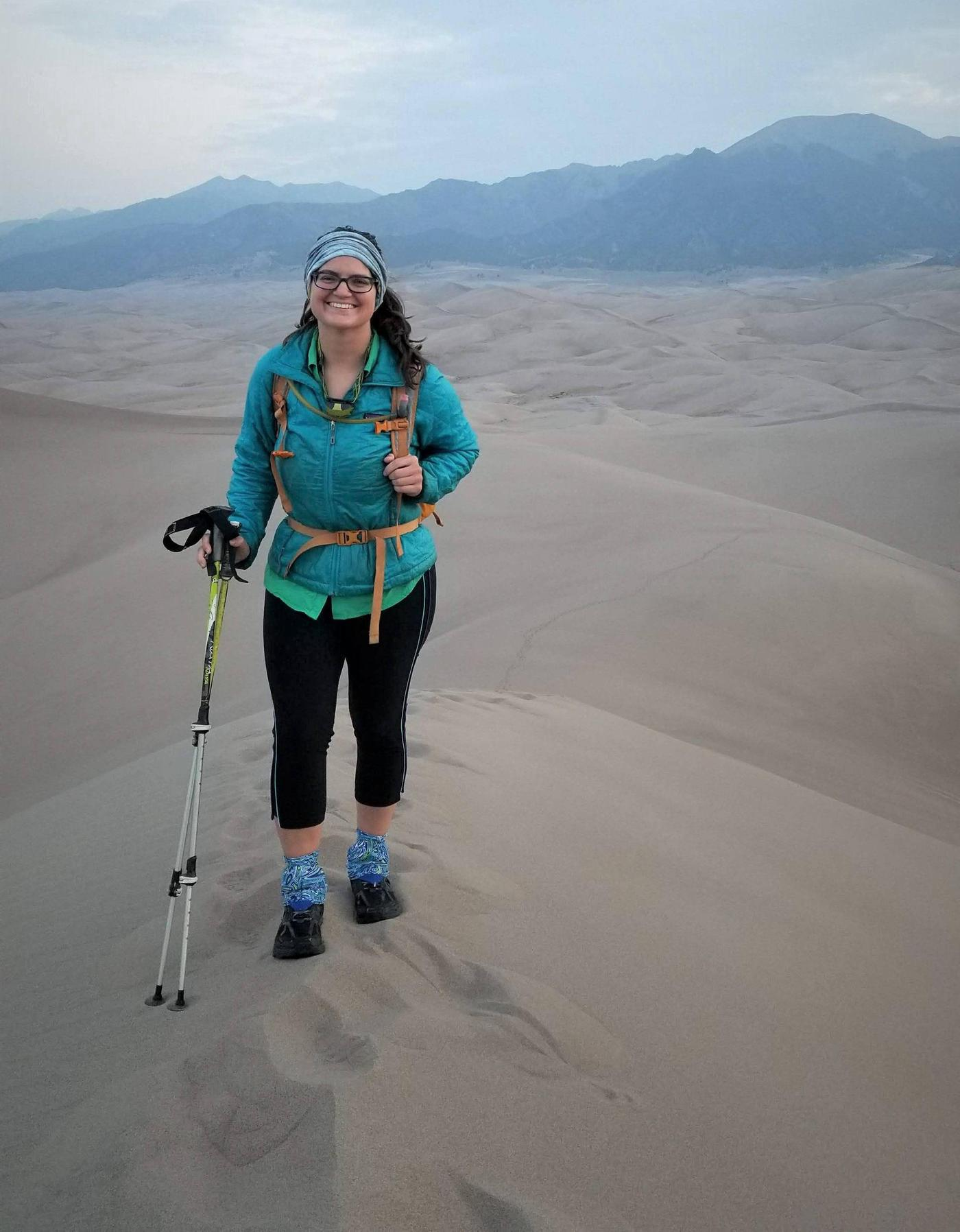 Backpacker on the dunes.A backpacker poses at the top of the high ridge line just outside the Day Use Area before entering the Dunes Backcountry in the summer of 2020.