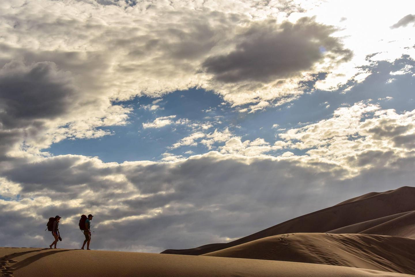 Two backpackers hiking in the dunes.Two backpackers climb over the high ridge line to camp in the Dunes Backcountry in the summer of 2020.