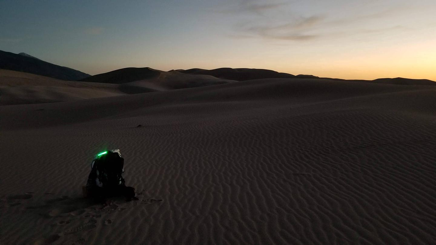 Backpack in the Dunes Backcountry at sunset.A lone backpack rests on the sand at sunset in the Dunes Backcountry.