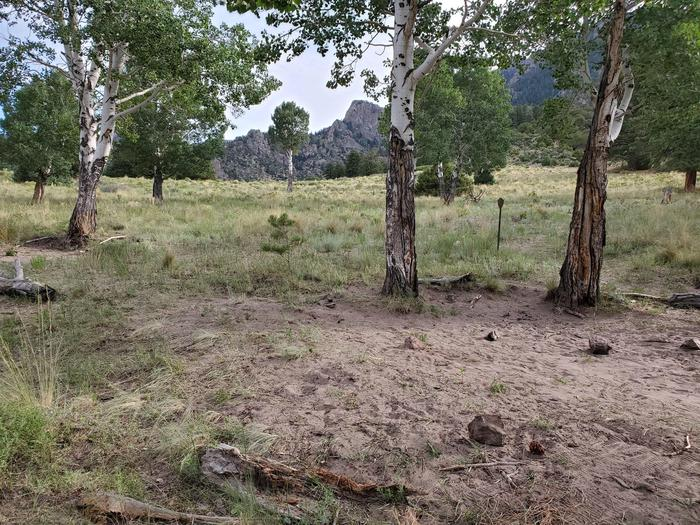 A flat sandy and grassy area surrounded by aspen trees, with a metal sign in the middle marking the Aspen campsite.Aspen is one of the designated backcountry sites, marked with a metal arrowhead sign.