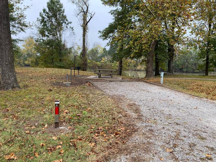 Site 2 - Bluff LandingThis site is partially shaded with a gravel drive/slab. The site comes equipped with a picnic table, grill and a firepit to enjoy while camping. Enjoy the view of the river with direct access down to the bank right behind the campsite.