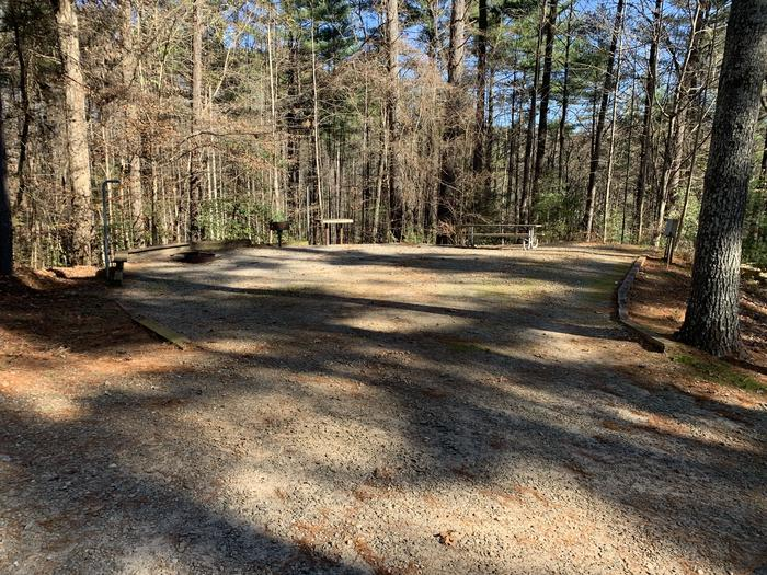 Gravel site surrounded by trees with fire pit, grill, table Large gravel site, fire pit, grill, table