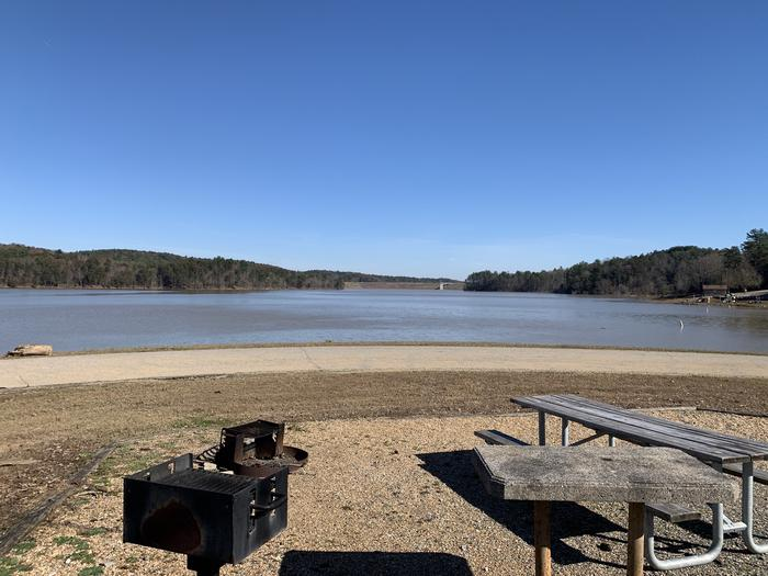 Gravel site with table, grill, fire pit, and views of dam tower across lake