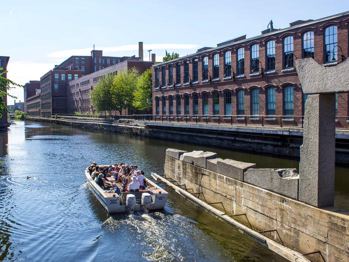 Group of visitors in an open top boat float on a canalGroup of visitors on a canal boat tour on the Pawtucket Canal
