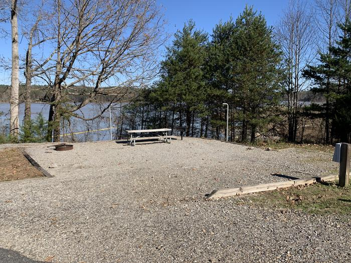 Shorter gravel pull in to site with grill, table, fire pit and next to swim beach