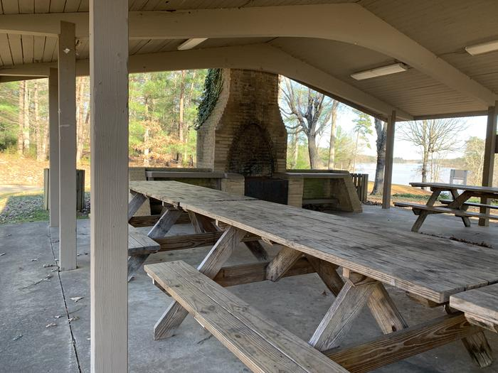 Large grill with chimney and rows of picnic tables Large grill under shelter and picnic tables