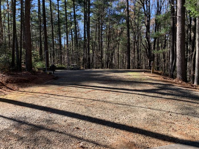 Gravel site with fire pit, table, grill, surrounded by tall pines Large gravel site with fire pit, table, grill