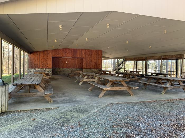 Rows of picnic tables and bathrooms under shelter