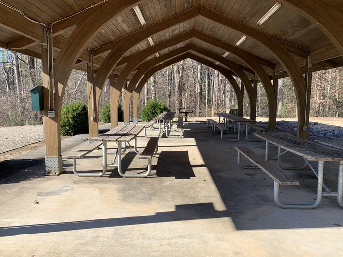 Rows of picnic tables and grill under shelter Picnic tables and grill