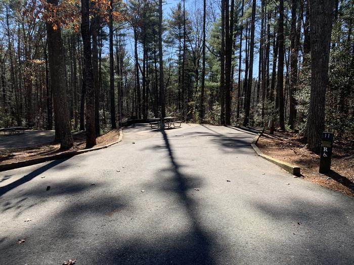 Large paved site that is wheelchair accessible surrounded by tall pines Wheelchair accessible paved site with fire pit, grill, table