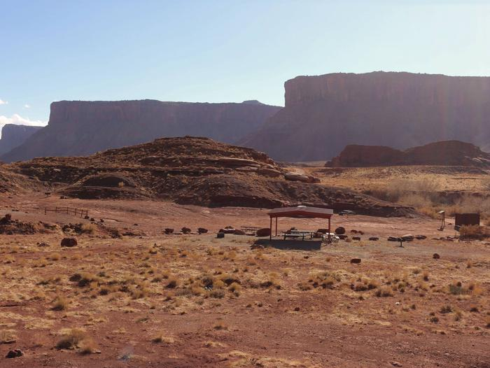 Plateaued cliffs in the background and group camp site in the foreground.