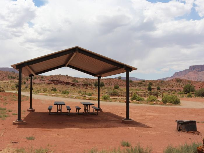 At the Upper Onion Creek Group Site a, two picnic tables sit underneath a large shade shelter with a fire ring  nearby and a horse corral in the distance. Wide open views of the Fisher Valley area surround the site. In the distance are large, red rock plateaus.