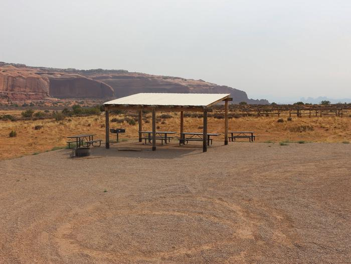 Lone Mesa Group Site A shade shelter, picnic tables, fire pit and parking area. Red rock cliffs in the distance.