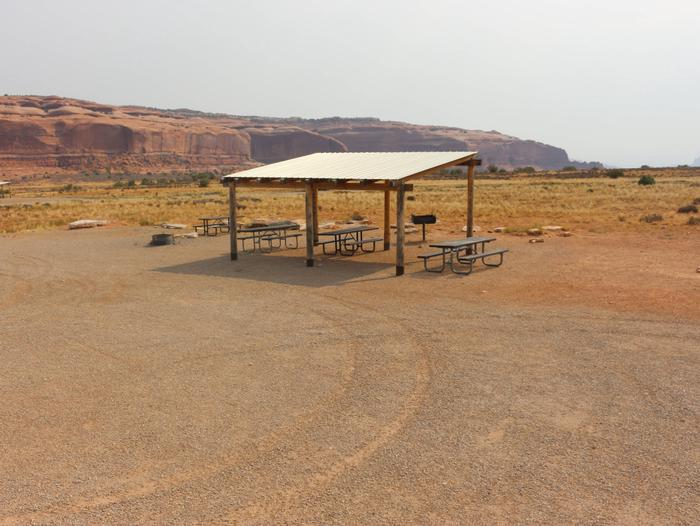 Lone Mesa Group Site E shade shelter, picnic tables, fire ring, and standing grill. Tall, red rock plateaus line the horizon.