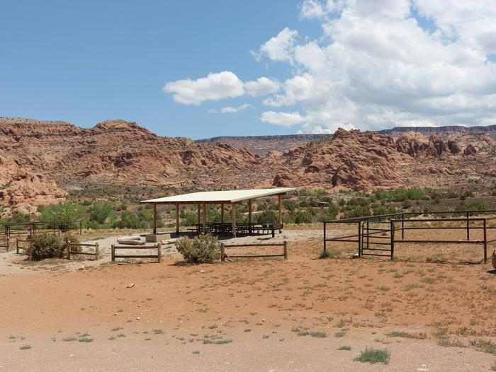 Ken's Lake Group Site A shade shelter, metal fence horse corral, and parking area with undulating, red, slick rock hills on the horizon.