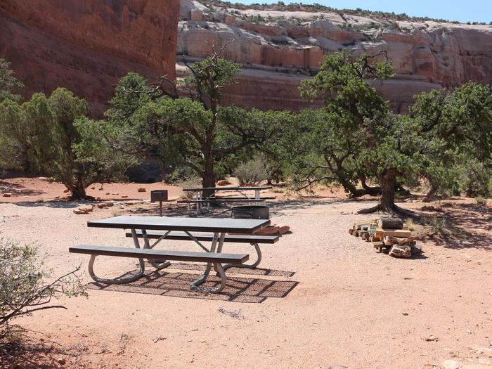 Windwhistle Group Site picnic tables, fire ring and tent area. Large slick rock walls line the horizon.