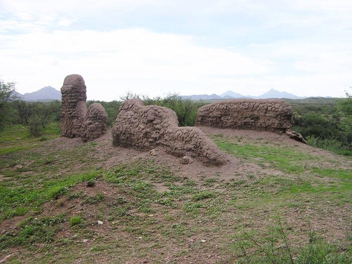 A mound and partial adobe walls of the ruins of Mission Los Santos Ángeles de Guevavi in the foreground and mountain peaks in the background. Los Santos Ángeles de Guevavi includes the only original Jesuit-era mission structures still standing above ground in Arizona.