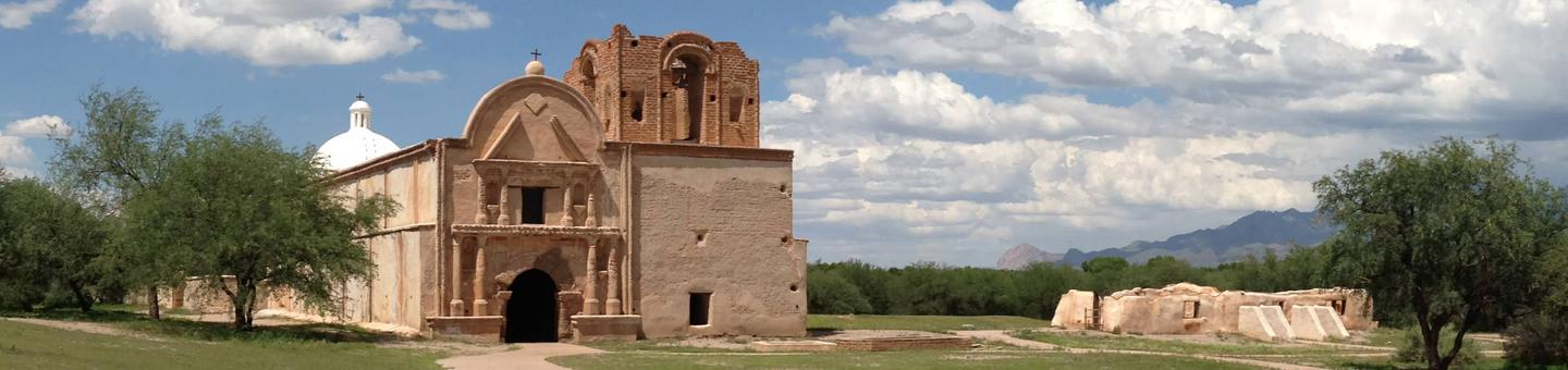 Tumacácori National Historical Park mission grounds, with the historic Franciscan mission church on the right and the convento ruin on the left. Mesquite bosque and mountains in the background. The Tumacácori mission church was built in the early 1800's and is maintained in a state of arrested ruin.  The goal is to preserve the original structure rather than additional restoration or speculative completion of architectural features.