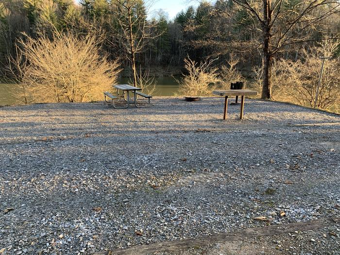 Gravel pull in and site with fire pit, table, grill