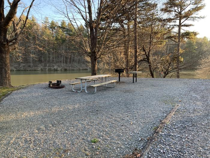 Gravel site with fire pit, table, grill and views of the lake Gravel site with fire pit, table, grill and lake views