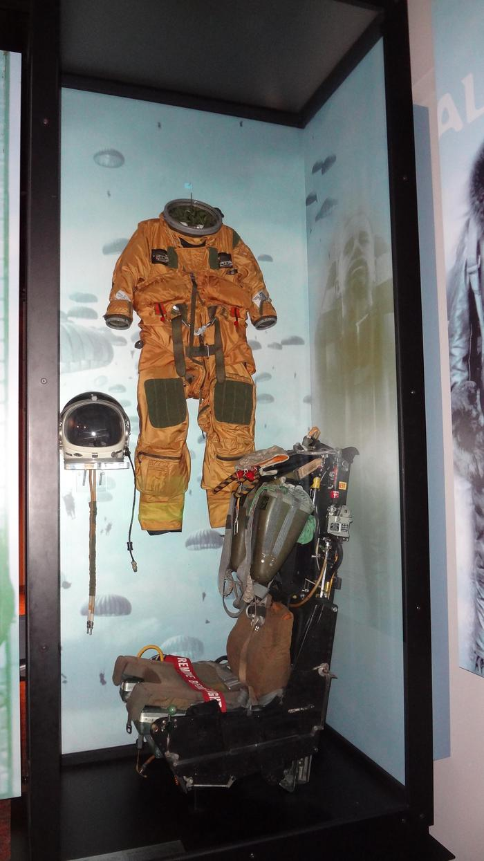 Flight suitAn ejection seat from an airplane in front of a flight suit.