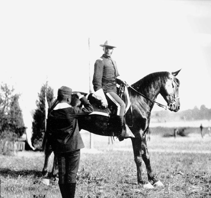 Charles Young on his mountCharles Young poses for a portrait with one of his horses as he is saluted by a young, unidentified boy.