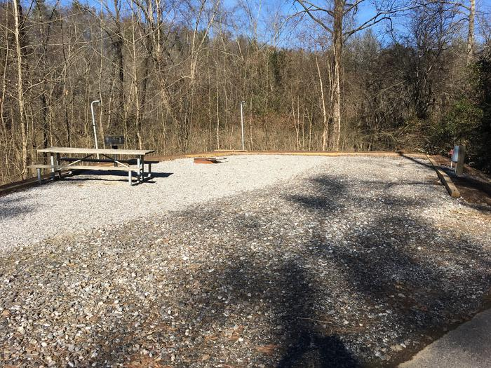 Short pull in with gravel site with fire pit, grill, table