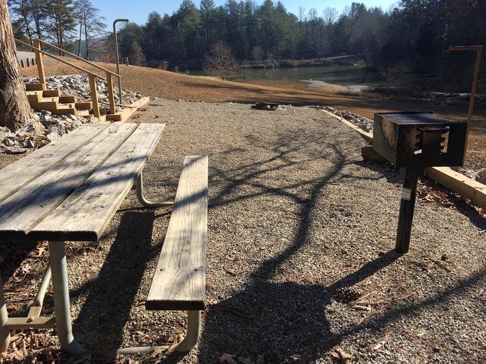 Gravel site with fire pit, table, grill and lake view