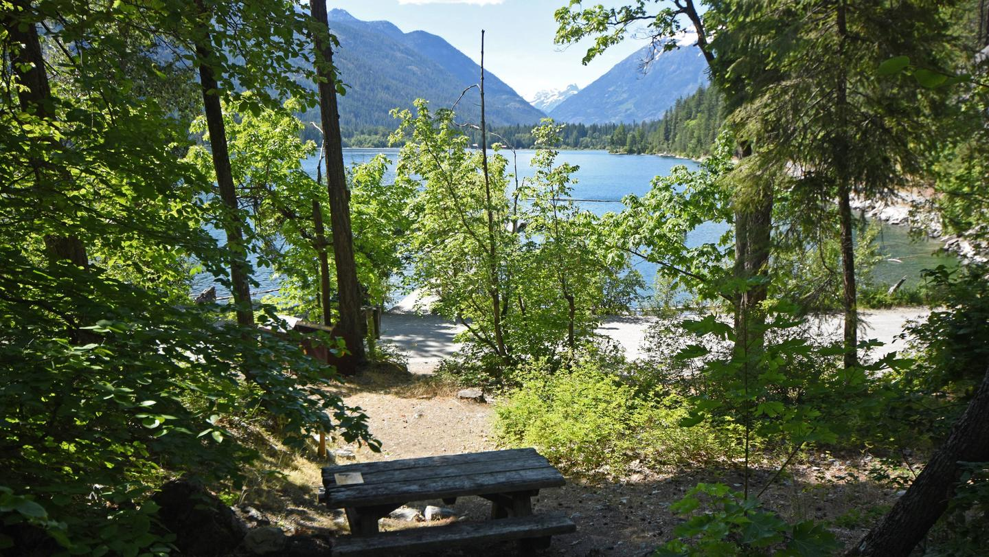 Picnic table with trees, lake, and mountains in the background. Campsite in Purple Point Campground.
