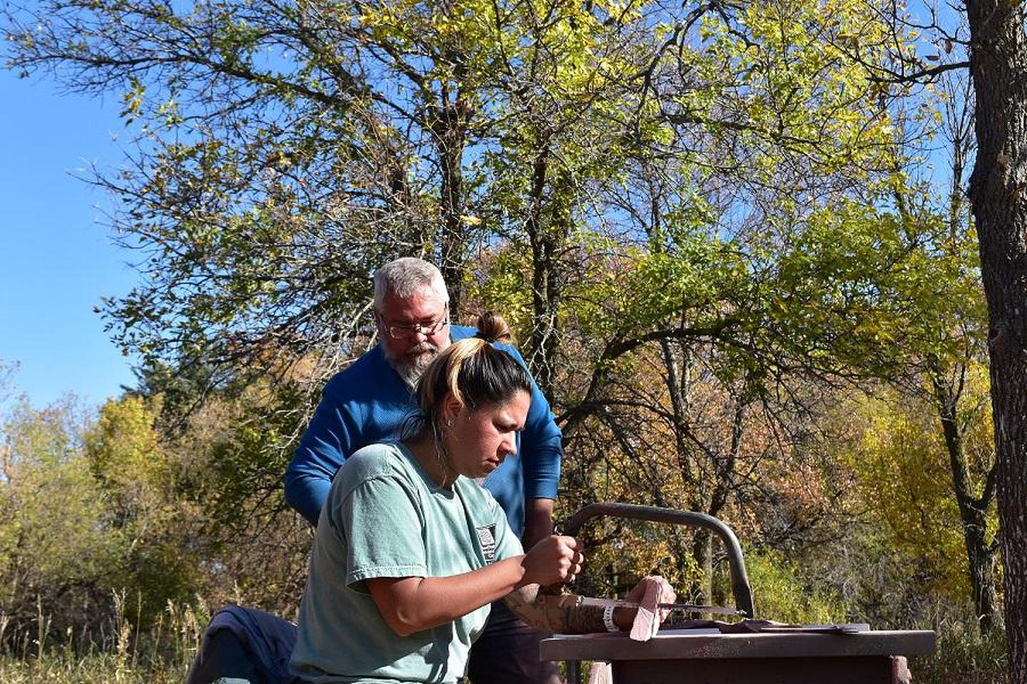 Learning to Carve PipestoneTravis Erickson teaches new carver, Jessica Arkeketa, how to make a pipe