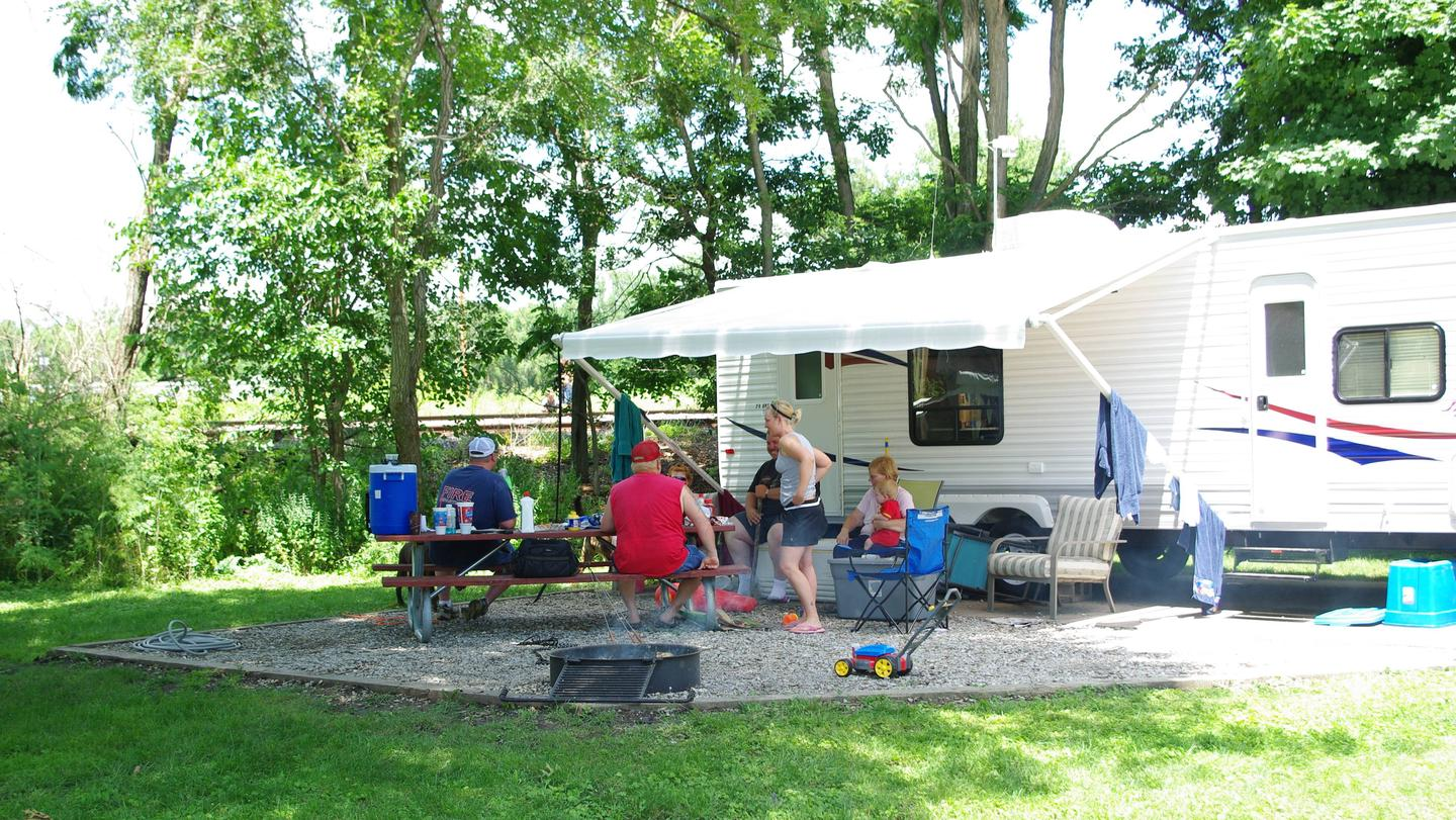 Campers visiting at campsite around picnic table.