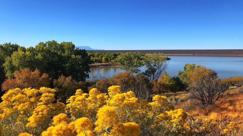 View of orange and red autumn trees surrounding Cochiti Lake Cochiti Lake in Autumn