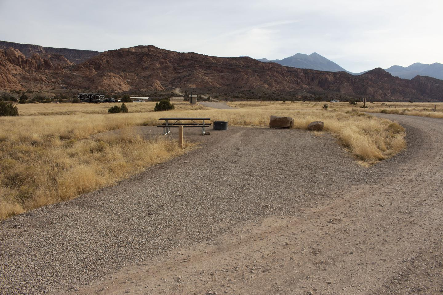 Camp site parking area, picnic table and fire ring with red rock cliffs and mountains in the background.