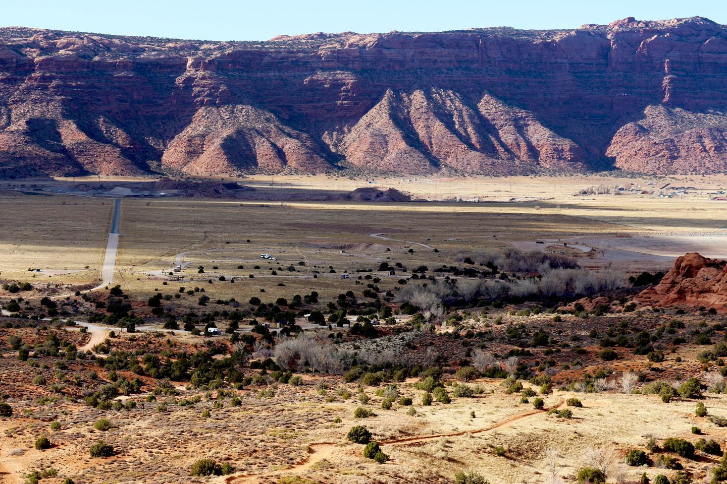 Overview of Ken's Lake Campground with desert cliffs in the background.