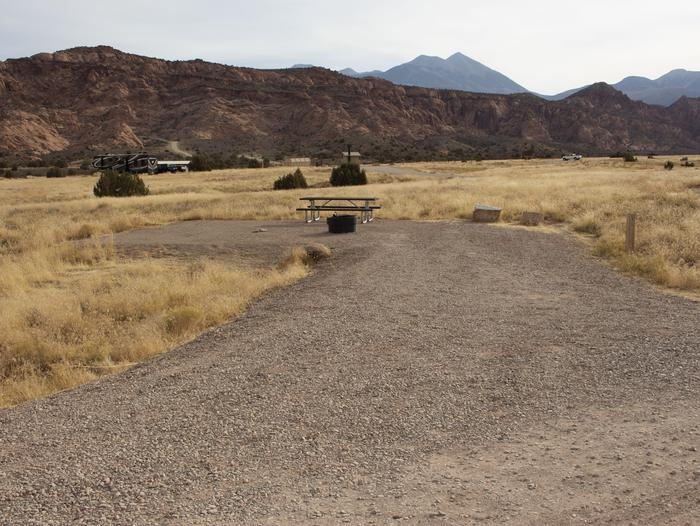 Campsite parking, picnic table, and fire ring with desert cliffs and mountains in the background.