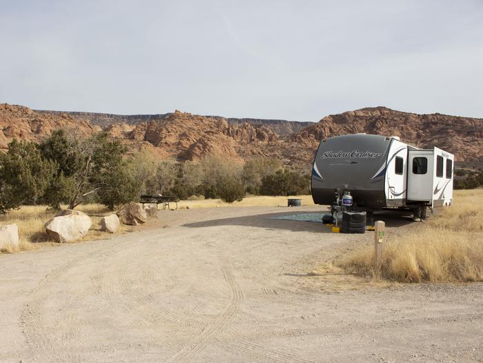 Campsite with trailer parking in parking area. Red rock cliffs line the horizon in the background.