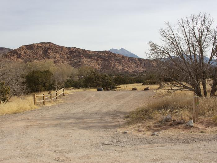 Campsite parking area, picnic table, and fire ring with red rock cliffs and mountains lining the horizon.